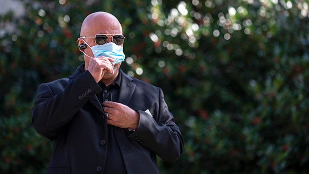A Guardian Ministry member adjusts his mask as he communicates with a team member via a radio earpiece as his team makes field sweeps outside of church before providing security for Sunday Mass at Good Shepherd Parish in Colleyville on December 6, 2020.
